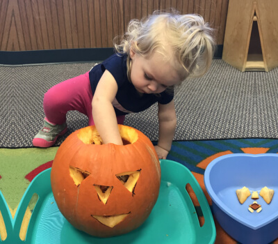 a kid playing with pumpkin